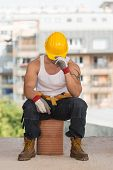 Tired Builder Resting On Brick