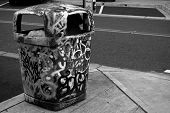 Lots of letters on trash can in black and white