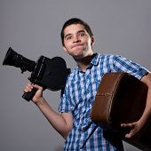 Portrait Of A Young Cameraman With Old Movie Camera And A Suitcase In His Hand.