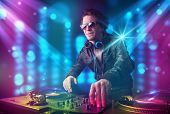 Young dj mixing music in a club with blue and purple lights