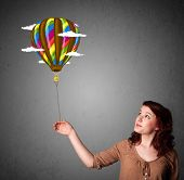 Young woman holding a balloon drawing with clouds