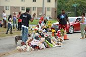 FERGUSON, MO/USA - AUGUST 30, 2014: A man raises hands at makeshift memorial where black teenager Michael Brown was shot to death by police in Ferguson, Missouri.