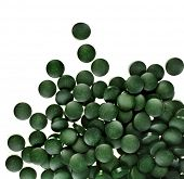Spirulina tablets algae nutritional supplement heap surface close up top view, isolated on white bac