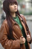 Image of young lady wearing brown leather jacket.