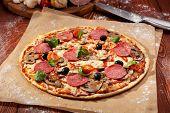 Pizza made with Salami, Mozzarella, Mushrooms, Olives and Tomato Sauce