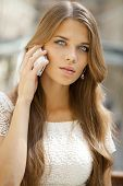 Portrait of a beautiful young woman calling by phone in shop