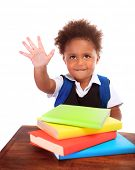 Happy African preschooler sitting behind desk with many books on it, isolated on white background, r