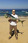 foto of mahi  - Happy tourist holding his big fish catch after fishing trip in Mexico - JPG