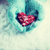 Woman hands in light teal knitted mittens are holding a beautiful red heart in a snow background. Lo