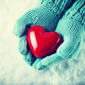Woman hands in light teal knitted mittens are holding a beautiful glossy red heart in a snow background. Love and St. Valentine concept.  Instagram filter.