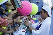 Professional tennis player Kei Nishikori signing autographs after practice for US Open 2014