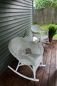 White wicker rocking chairs on wood porch