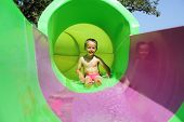 Child sliding down a water slide at a water park smiling and having fun
