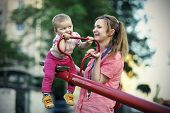 foto of seesaw  - Small girl with her mother playing on the seesaw - JPG