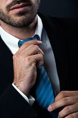 Businessman Without Face Straightens Tie Yourself. Isolated On Black.
