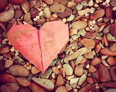 a discarded paper heart on a rock background toned with a retro vintage instagram filter effect