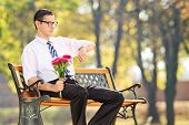 Young man holding flowers and checking the time seated on bench in park
