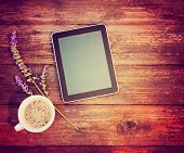 a tablet with a cup of coffee and a flower on a wooden texture background toned with a retro vintage instagram filter