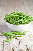 green string beans in a bowl on rustic wooden table
