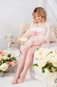 Beautiful Pregnant Woman In A Lace Negligee Sitting On A Bed Of Flowers