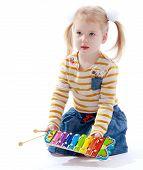 Little girl holding a children's musical instrument.