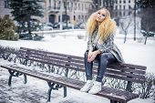 Golden haired woman on a bench