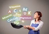 stock photo of minerals  - Pretty young woman cooking vitamins and minerals - JPG