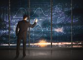 Businessman drawing business graphs on glass wall