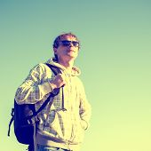 Stylized colorized vintage fashion portrait of happy man hiker holding backpack and looking at the s