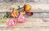 Dry Rose And The Condom On Wooden Background