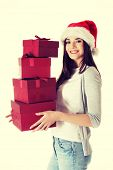 Young woman in santa hat holding stack of presents.