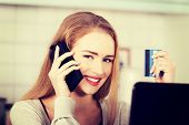 Beautiful woman talking through phone and working with laptop.