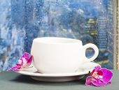 Coffee cup and pink orchid on a rainy day in front of the wet city window