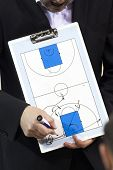 Basketball coach with clipboard explaining schemes during timeout