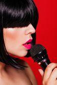 Closeup portrait of beautiful woman listening to music on headphones enjoying a singing. Karaoke