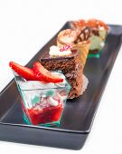 picture of fancy cake  - delicious strawberry cake with cream in front of little chocolate and coffee cakes on black dish - JPG