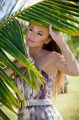 Portrait Of Beautiful Woman Behind Palm Frond