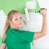Young Woman With Paint Roller In Hand