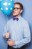 Attractive young man with a blue balloon in his hand. Party, birthday, Valentine