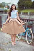 Young Beautiful, Elegantly Dressed Woman With Bicycle In The Park Or Outdoor
