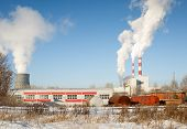 industrial park with chimney and white smoke on blue sky