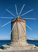 A Stone Retro Windmill On Background Of Blue Sea