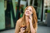 Teenager eating muffin looking in phone