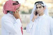 stock photo of people talking phone  - Arabic Gulf people talking on cell phone - JPG