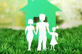Cutout paper family and house on green grass and bright blurred background