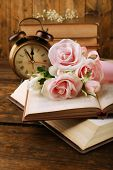 Books with flowers and clock on wooden background