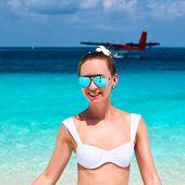Woman in bikini at tropical beach. Seaplane at background.