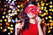 Beautiful girl with masquerade mask and glass of champagne on bright background