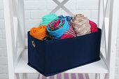 Different scarves in textile box on shelf and white brick wall background