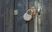 Old rusty padlock on wooden gate